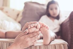 Mother is rubbing the barefeet of sick asian child girl. To reduce the fever with love and care Stock Image