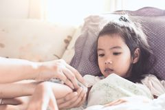 Mother is rubbing the body of sick asian child girl. To reduce the fever with love and care royalty free stock image
