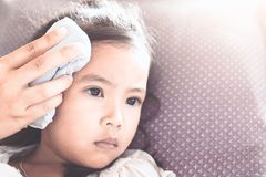 Mother is rubbing the body of sick asian child girl. To reduce the fever with love and care stock image
