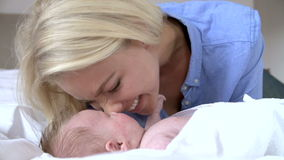 Mother Rubbing Noses With Baby In Bed stock video
