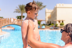 Mother rubbing in sunscreen on her son Royalty Free Stock Image