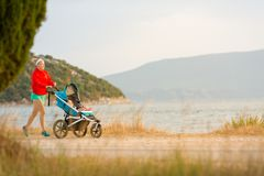 Mother running with stroller, enjoying motherhood at sunset land. Mother with child in stroller running and enjoying motherhood at sunset and mountains landscape stock photography