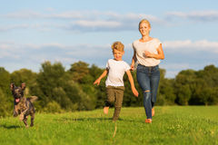 Mother runs with her boy and a dog on a meadow Royalty Free Stock Images