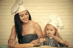 Mother`s assistant. Woman and boy in chef hats. Mother and child son rolling dough with pins. Happy family in kitchen on white brick wall. Homemade baking and Stock Image