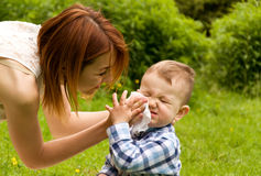 Mother's care. toddler unhappy mom cleans his face. With a napkin Royalty Free Stock Images
