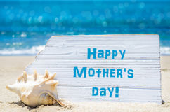 Mother`s day background with seashell on the sandy beach Royalty Free Stock Photo