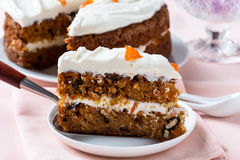Mother's day carrot cake with swirls cream cheese frosting. Mother's day carrot cake, homemade moist and sweet layer cake with grated carrot, walnuts and dried royalty free stock photos