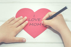 Mother's Day. Child typing on a heart for Mother's Day Stock Photo