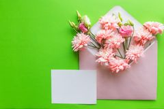 Mother`s Day concept. Bouquet of pink lisianthus, chrysanthemums with envelope. Blank paper note for copy space.card in. Mother`s Day concept. Bouquet of pink stock images