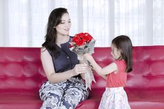 Mother`s day concept: Daughter gives a bouquet of red roses to mother.  Stock Photos