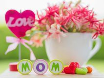 Mother`s day concept. LOVE MOM alphabet. With colorful heart and flower on background stock image