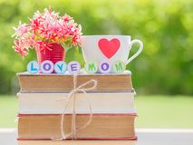 Mother`s day concept. LOVE MOM alphabet. On stack of books, gifts, tea cup with red heart and flower on background Royalty Free Stock Photo