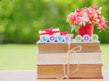 Mother`s day concept. LOVE MOM alphabet on stack of books, gifts, tea cup with red heart and flower on background Royalty Free Stock Image