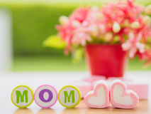 Mother`s day concept. MOM alphabet with marshmallow in the shape of heart and flower on background Stock Image
