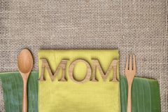 Mother`s day concept, mom wooden text design on yellow napkin. With wooden fork and spoon on hessian texture background royalty free stock photography