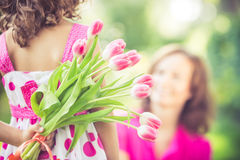 Mother's day. Mother and daughter with bouquet of flowers against green blurred background. Spring family holiday concept. Mother's day