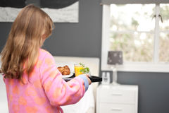 Mother's day, a daughter carries a tray of breakfast to her mum Royalty Free Stock Image