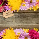 Mother's Day flower frame with tag against wood Royalty Free Stock Photo