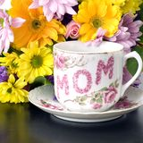 Mother's day flowers square. Pink and Red and white mother's day collectible tea cup or coffee cup mug sitting in front of a bouquet of spring flowers including royalty free stock image