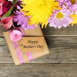 Mother's Day gift box with flowers on wood Royalty Free Stock Photo
