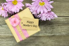 Mother's Day gift box on wood with daisies Royalty Free Stock Image