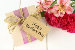 Mother's Day gift with flowers on white wood Royalty Free Stock Photography