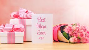 Mother`s Day gift, pink roses and Best Mom Ever greeting card on table. Happy Mother`s Day gift, pink roses and Best Mom Ever greeting card on table Royalty Free Stock Images