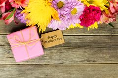 Mother's Day gift with tag and flowers on wood Royalty Free Stock Image