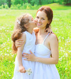 Mother's day and happy family concept - child kissing loving mom Royalty Free Stock Photos