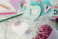 Mother`s day holiday, composition of the word love from bulk letters, decor, paper, pencils on the table. Top view stock photography