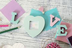 Mother`s day holiday, composition of the word love from bulk letters, decor, paper, pencils on the table. Top view stock photo