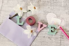 Mother`s day holiday, composition of the word love from bulk letters, fresh flowers, envelope, paper, pencils on the table royalty free stock photo