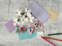 Mother`s day holiday, composition of the word love from bulk letters, fresh flowers, envelope, paper, pencils on the table. Top view stock images