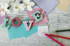 Mother`s day holiday, composition of the word love from bulk letters, fresh flowers, envelope, paper, pencils on the table. Top view royalty free stock photos