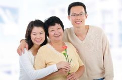 Mother's day at home. Asian family at home. Adult offsprings giving carnation flowers to senior mother Royalty Free Stock Photos