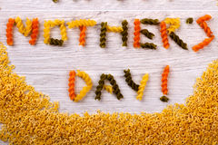 Mother`s Day pasta formed text. Greeting words on wooden surface. Beauty of creativity. Food as decorative element stock photo