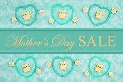 Mother`s Day Sale message with teal frame hearts, teddy bears and rose buds on a teal plush fabric