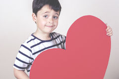 Mother's Day. Smiling boy with a red heart for the Mother's Day Stock Images
