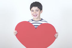 Mother's Day. Smiling boy with a red heart for the Mother's Day Royalty Free Stock Photo