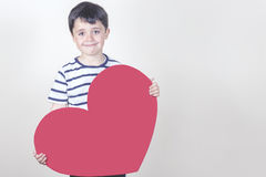 Mother's Day. Smiling boy with a red heart for the Mother's Day Stock Image