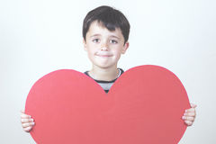 Mother's Day. Smiling boy with a red heart for the Mother's Day Royalty Free Stock Photography