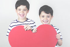Mother's Day. Smiling boys with a red heart for the Mother's Day Royalty Free Stock Image