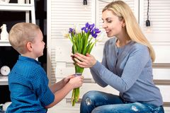 Son congratulates his beloved mother and gives her a bouquet of tulips.The concept of the celebration,women`s day.Mother`s Day. stock photo