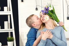 Son congratulates his beloved mother and gives her a bouquet of tulips.The concept of the celebration,women`s day.Mother`s Day. royalty free stock image