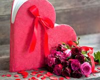 Red roses for the holiday of love and happiness. Mother`s Day, St. Valentine`s Day, birthday, red roses on a wooden table and a gift stock images