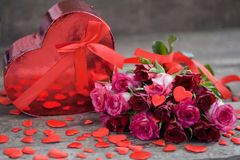 Red roses for the holiday of love and happiness. Mother`s Day, St. Valentine`s Day, birthday, red roses on a wooden table and a gift stock photos