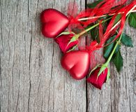 Red roses for the holiday of love and happiness. Mother`s Day, St. Valentine`s Day, birthday, red roses on a wooden table and a gift royalty free stock image