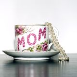 Mother's day tea cup pearls sq. Antique Red and white mother's day collectible tea cup with string of white pearls on white background and black table as stock images