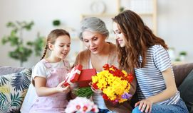 Mother`s day! three generations of  family mother, grandmother and daughter congratulate on the holiday, give flowers stock photography