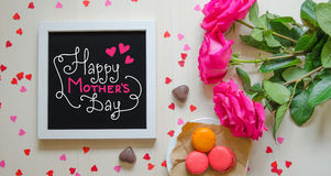 Mother`s Day vintage composition of white photo frame with greeting quote. Pink roses bouquet, macarons and paper hearts. Top view Royalty Free Stock Image
